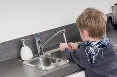 Bambino che si lava le sue mani Fotografia Stock