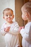 Bambino che si leva in piedi contro lo specchio Fotografia Stock Libera da Diritti