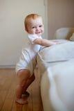 Bambino che si leva in piedi in su contro uno strato Fotografie Stock