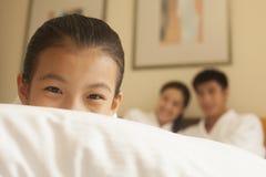 Bambino che si nasconde dietro il cuscino Fotografia Stock