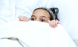 Bambino che si nasconde dietro la coperta mentre guardando film Immagine Stock