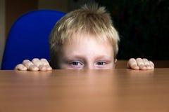 Bambino che si nasconde sotto la tavola Immagini Stock