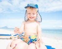 Bambino che si siede alla madre sulla spiaggia Fotografia Stock