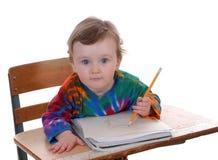 Bambino che si siede allo scrittorio del banco Fotografie Stock