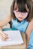 Bambino che si siede allo scrittorio del banco con i vetri Immagini Stock Libere da Diritti