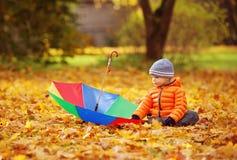 Bambino che si siede con l'ombrello nel bello giorno autunnale immagini stock libere da diritti