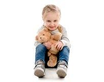 Bambino che si siede e che abbraccia orsacchiotto, isolato Fotografia Stock