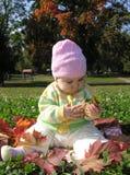 Bambino che si siede in fogli fotografia stock
