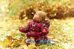 Bambino che si siede in fogli di autunno Immagine Stock