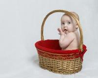 Bambino che si siede nel cestino del regalo di natale Immagini Stock
