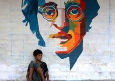 Bambino che si siede nell'ambito dei graffiti Fotografia Stock Libera da Diritti