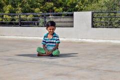 Bambino che si siede nell'ambito della luce luminosa del sole che posa per un'immagine immagine stock