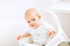 Bambino che si siede nella presidenza del bambino e che fa fronte divertente fotografie stock