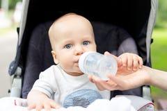 Bambino che si siede in passeggiatore ed acqua potabile dalla bottiglia durante la passeggiata al giorno di estate caldo Mamma ch immagini stock