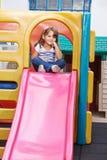 Bambino che si siede sopra uno scorrevole fotografia stock