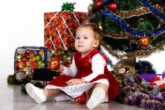 Bambino che si siede sotto un albero di Natale Fotografie Stock