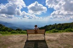 Bambino che si siede su un banco con le nuvole nei precedenti Fotografie Stock