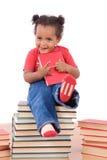 Bambino che si siede su un mucchio dei libri Fotografia Stock Libera da Diritti