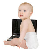 Bambino che si siede su una priorità bassa bianca con il computer portatile Fotografia Stock Libera da Diritti