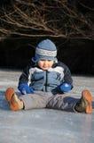 Bambino che si siede sul ghiaccio Fotografie Stock Libere da Diritti