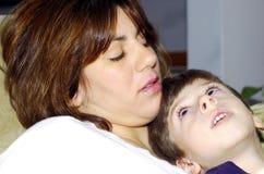 Bambino che si siede sul giro delle mamme Fotografia Stock