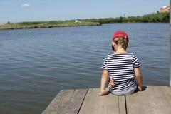 Bambino che si siede sul ponte di legno Fotografia Stock