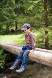 Bambino che si siede sul ponte in natura Immagini Stock Libere da Diritti