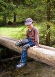 Bambino che si siede sul ponte in natura Fotografia Stock