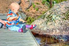 Bambino che si siede sul ponticello Fotografie Stock