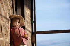 Bambino che si siede sul punto nel villaggio Immagini Stock