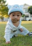 Bambino che si siede sull'erba Fotografia Stock