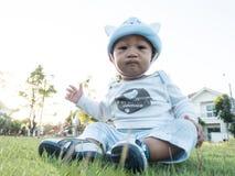 Bambino che si siede sull'erba Immagini Stock