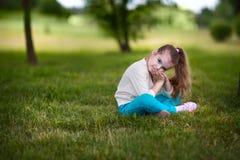 Bambino che si siede sull'erba Fotografia Stock Libera da Diritti