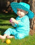 Bambino che si siede sull'erba che gioca con la sfera colorata Fotografie Stock
