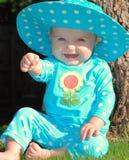 Bambino che si siede sull'erba in un'attrezzatura del polkadot immagini stock