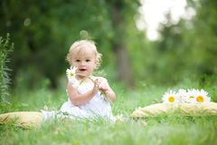 Bambino che si siede sull'erba verde Fotografie Stock Libere da Diritti