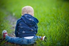 Bambino che si siede sull'erba verde Fotografie Stock