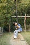 Bambino che si siede sulla cabina di funivia del giocattolo in un campo da gioco per bambini fotografia stock