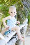 Bambino che si siede sulla palma Immagini Stock
