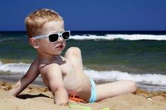 Bambino che si siede sulla spiaggia in sabbia. ragazzino vicino al mare Immagini Stock
