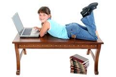 Bambino che si siede sulla Tabella che lavora al computer portatile fotografia stock libera da diritti