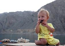 Bambino che si siede sulla tavola Fotografia Stock