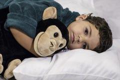 Bambino che si situa a letto Immagini Stock