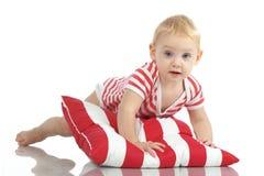 Bambino che si trova con il cuscino Fotografia Stock
