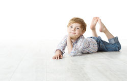 Bambino che si trova giù sul pavimento e che esamina macchina fotografica Immagine Stock