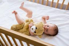 Bambino che si trova sul letto di bambino fotografia stock libera da diritti