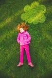 Bambino che si trova sull'erba verde in parco sotto la nuvola di illuminazione Immagini Stock