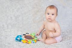 Bambino che si trova sulla coperta di sviluppo giocando nel cellulare Giocattoli educativi Bambino dolce che striscia e che gioca immagini stock libere da diritti