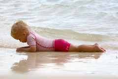 Bambino che si trova sulla spiaggia Fotografia Stock