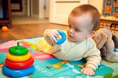 Bambino che si trova sulla sua pancia e che gioca con la piramide Fotografia Stock
